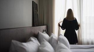 Nainen katsoo ikkunasta Solo Sokos Hotel Paviljongin huoneessa