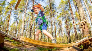 Маленький ребенок идет по подвесному мосту в веревочном парке развлечений Вуокатти.