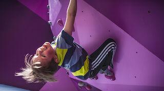 Ребенок карабкается по бутовой стенке в «Superpark» Вуокатти