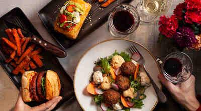 Burger -ateria, burrito sekä salaatti ja viiniä sekä punaisia neilikoita ruokapöydällä.