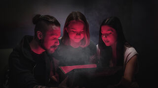 Kolme henkilöä pakohuoneessa keskittyneenä mystisen arkun ympärille hämyisessä tunnelmassa.