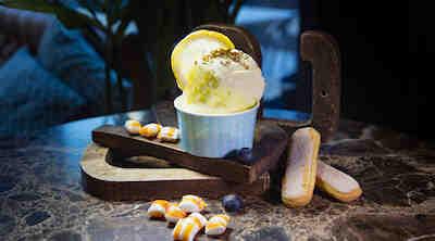 Italialaistyylinen jäätelö koristeltuna citrushedelmän siivulla.