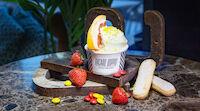 Italialaistyylinen jäätelö koristeltuna citrushedelmän siivulla, suklaamakeisillas sekä tuoreilla mansikoilla..