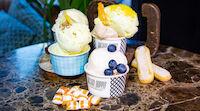 Aseltelma Italialaistyylistä jäätelöä koristeltuna tuoreilla marjoilla ja hedelmillä sekä makeisilla.