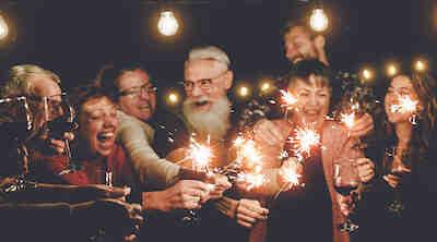 Iloinen joukko ihmisiä nauttimassa iltaa viinin parissa.