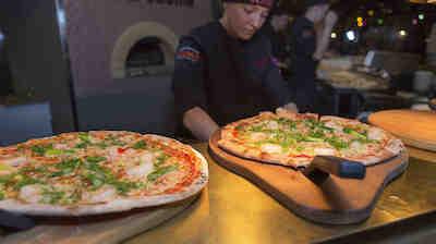 Pizzakokki täyttää pizzat